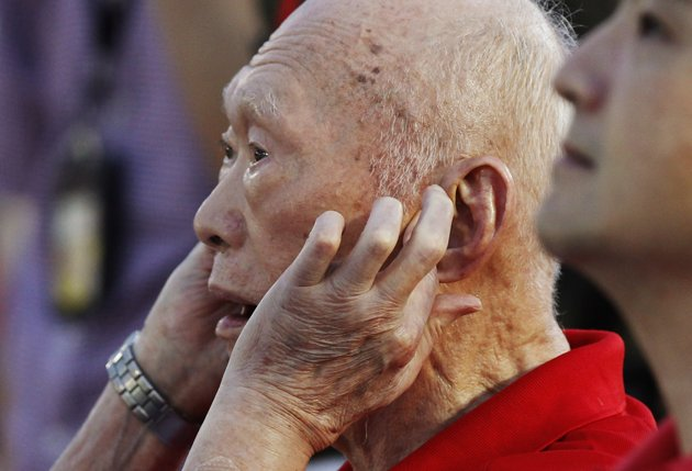 Singapore's former Prime Minister Lee Kuan Yew covers his ears as fighter jets fly past for an aerial display during Singapore's national day parade celebrations August 9, 2013