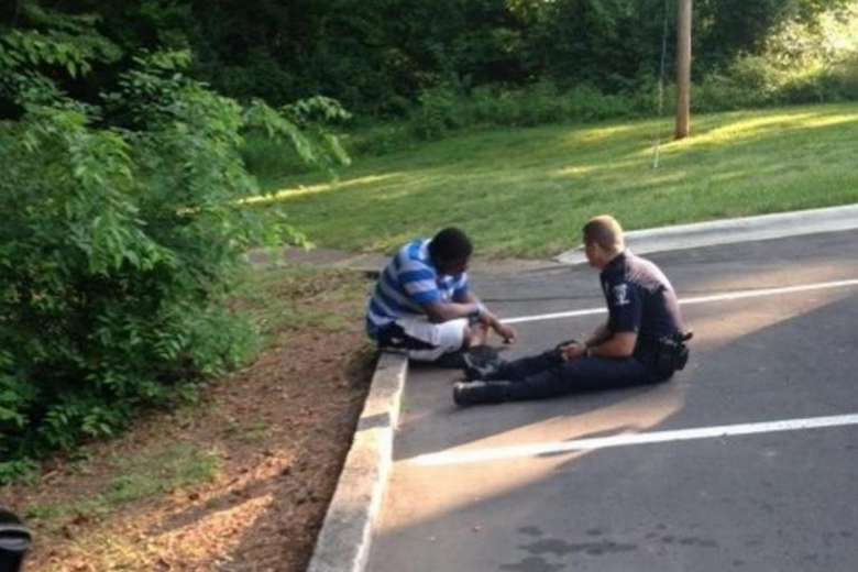 Police officer Tim Purdy chatting with the teenager, who had wandered away from his high school campus. PHOTO: FACEBOOK/CHARLOTTE-MECKLENBURG POLICE DEPARTMENT (Via straitstimes.com)