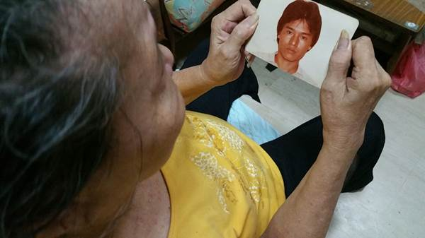 Patrick's mother holding onto his photograph. (Source: the family of the Late Patrick Lee.)
